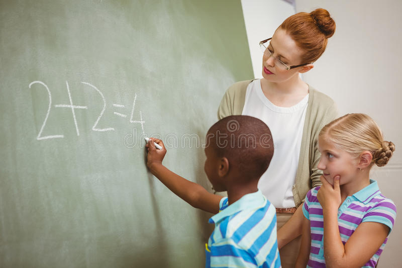 Insegnante che assiste ragazzo per scrivere sulla lavagna in aula fotografia stock