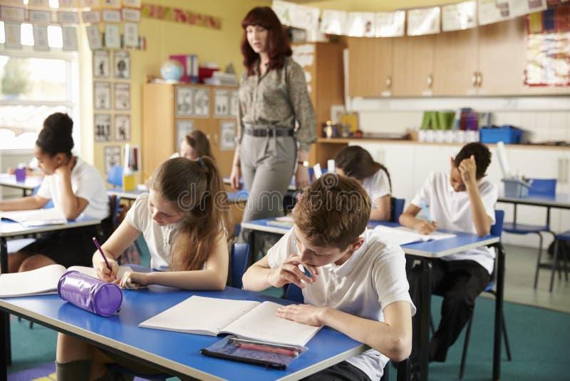 Insegnante che cammina nella sua aula occupata della scuola primaria fotografia stock libera da diritti
