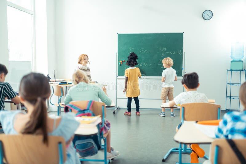 Insegnante che guarda la sua classe mentre una scrittura di due bambini fotografia stock