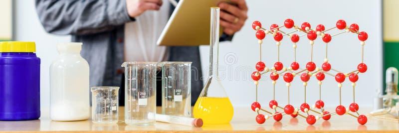 Insegnante che per mezzo della compressa digitale per insegnare agli studenti nella classe di chimica Istruzione, VR, ripetizioni fotografia stock