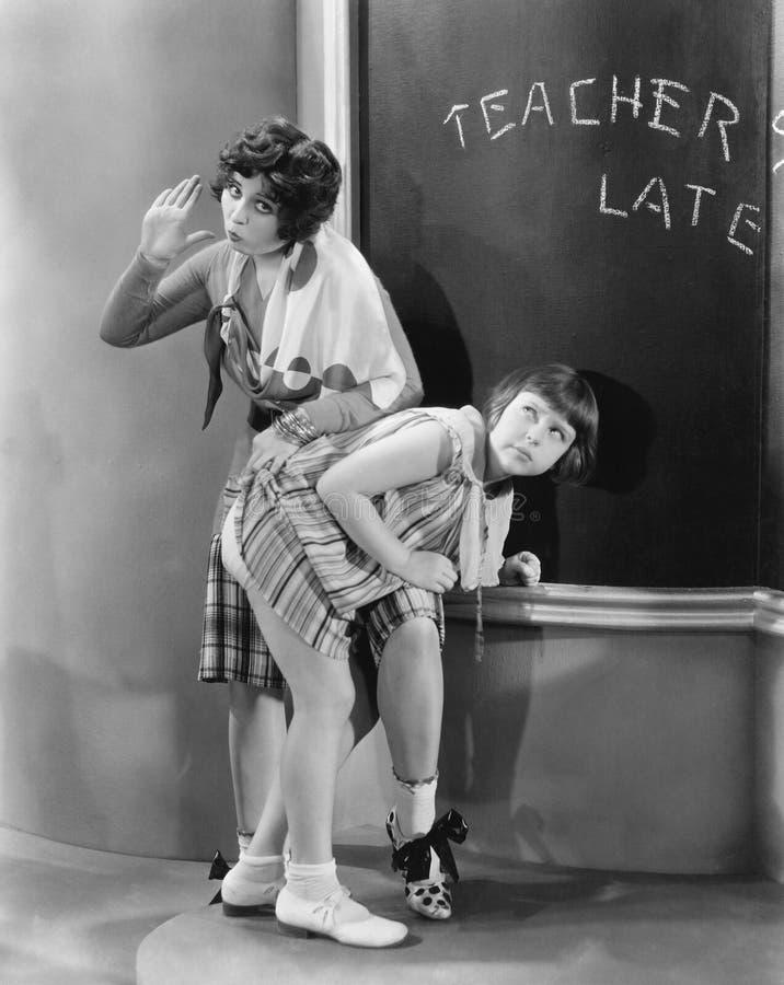 Insegnante che sculaccia una ragazza in un'aula (tutte le persone rappresentate non sono vivente più lungo e nessuna proprietà es immagini stock
