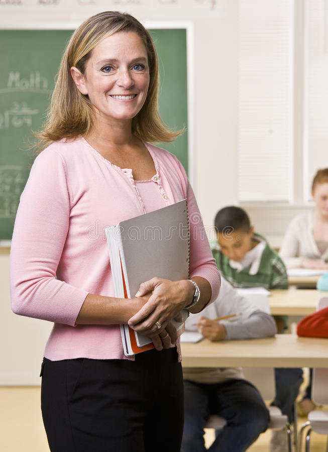 Insegnante che si leva in piedi con il taccuino in aula fotografia stock libera da diritti