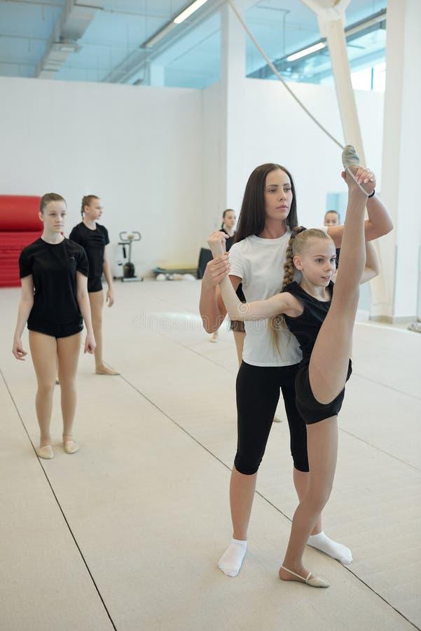 Insegnante cheerleader che sostiene una ragazza che si divide in piedi in verticale fotografia stock libera da diritti