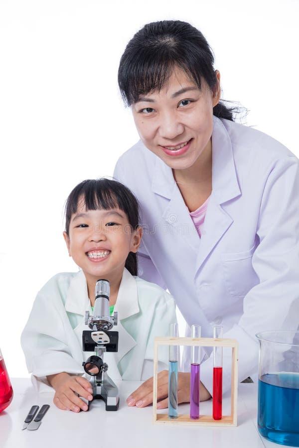 Insegnante cinese asiatico e piccola ragazza dello studente che lavorano con il micro fotografia stock