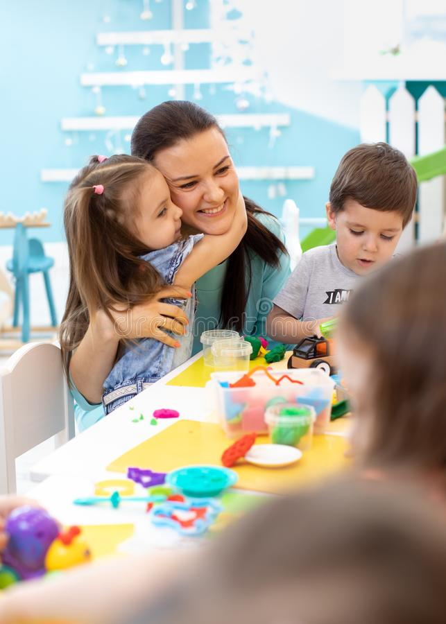 Insegnante con i bambini che lavorano con il plasticine all'asilo o al playschool immagine stock libera da diritti