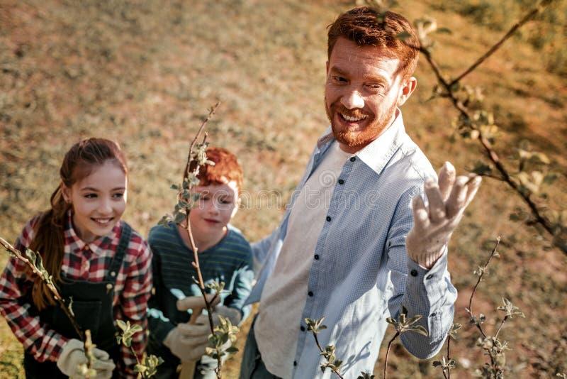 Insegnante dai capelli rossi con la barba che mostra come coltivando gli alberi fotografie stock