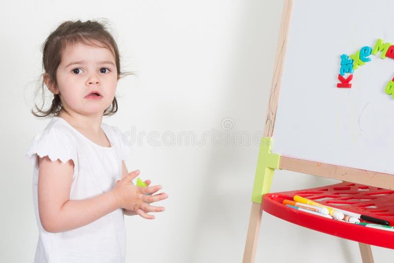 insegnante del gioco della ragazza del bambino con la lavagna del giocattolo a scuola fotografie stock libere da diritti