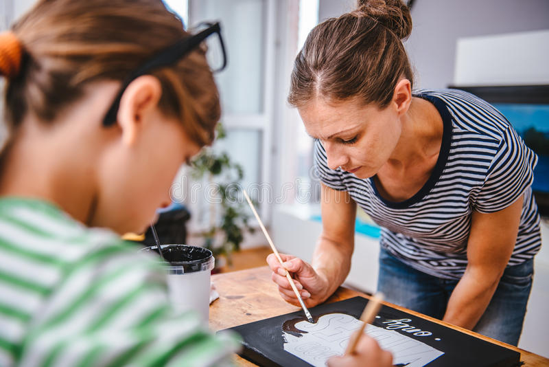 Insegnante di arte che aiuta uno studente con pittura immagine stock
