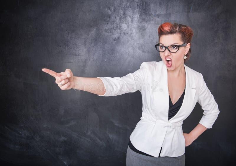 Insegnante di grido arrabbiato che precisa sul fondo della lavagna immagini stock libere da diritti