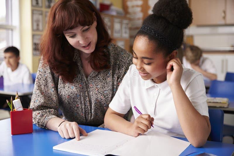 Insegnante di scuola primaria con una scolara nella classe, fine su immagine stock libera da diritti
