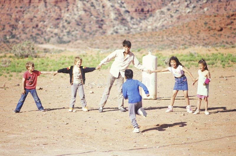 Insegnante e bambini che giocano un gioco fotografie stock