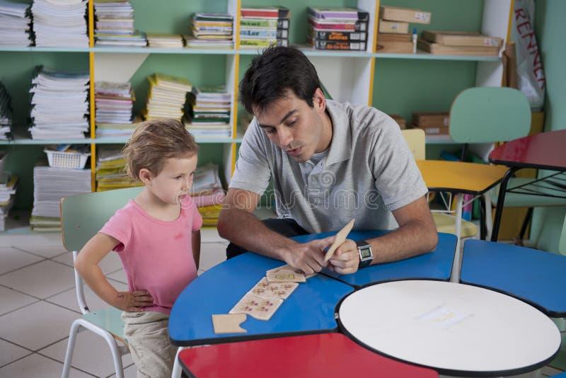 Insegnante e bambino prescolari nell'aula fotografie stock libere da diritti