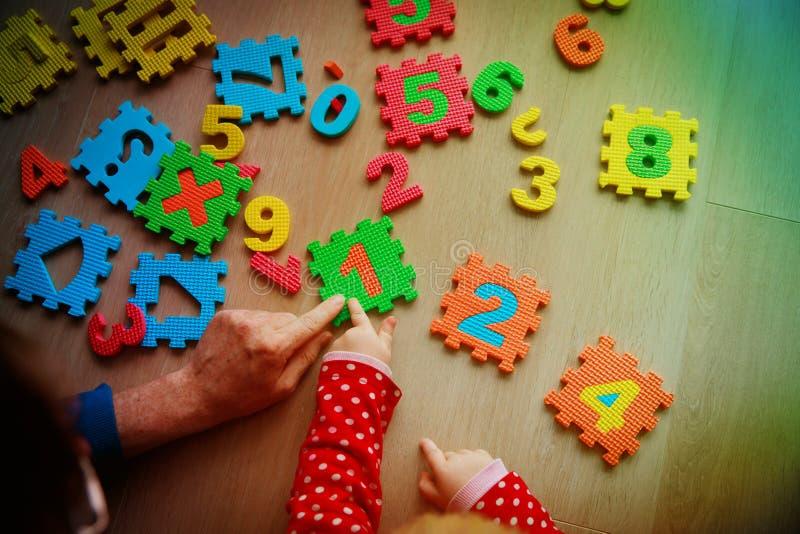 Insegnante e gioco da bambini con il puzzle di numero fotografia stock
