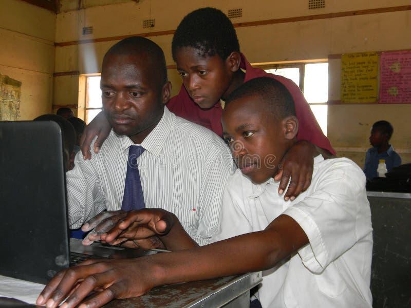 Insegnante e studenti con il computer fotografia stock libera da diritti