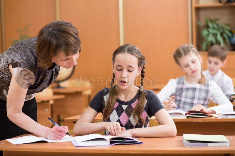 Insegnante ed allievi in aula che imparano insieme Lo scolaro guarda insieme all'insegnante in libro Ciò dice a bambino il compit fotografia stock libera da diritti