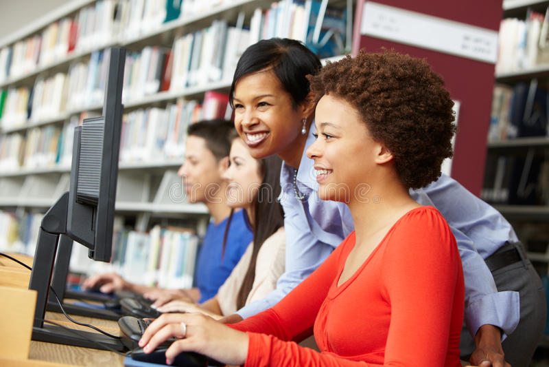 insegnante ed allievi che lavorano ai computer fotografia stock libera da diritti
