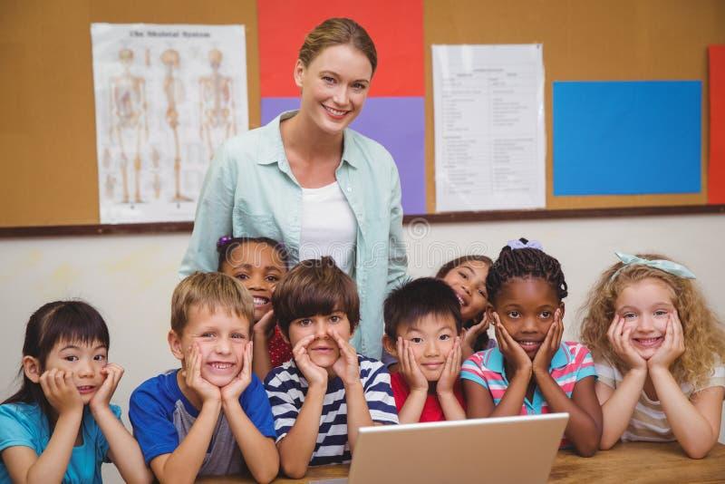 Insegnante ed allievi che lavorano al computer portatile fotografia stock libera da diritti