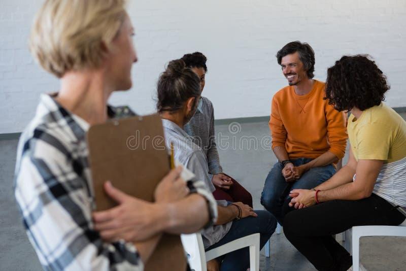 Insegnante femminile che esamina gli studenti che parlano mentre sedendosi sulla sedia fotografie stock libere da diritti