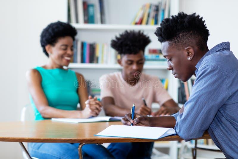Insegnante femminile che impara con gli studenti afroamericani fotografie stock
