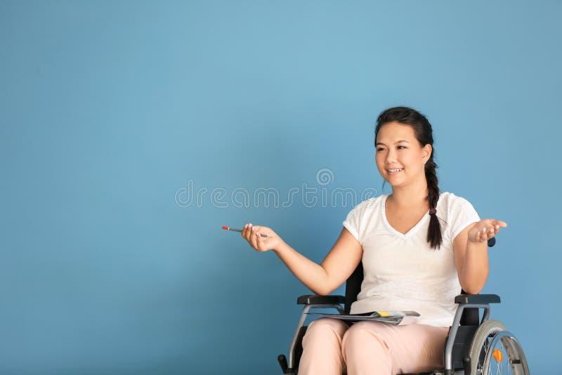 Insegnante femminile in sedia a rotelle sul fondo di colore immagine stock libera da diritti