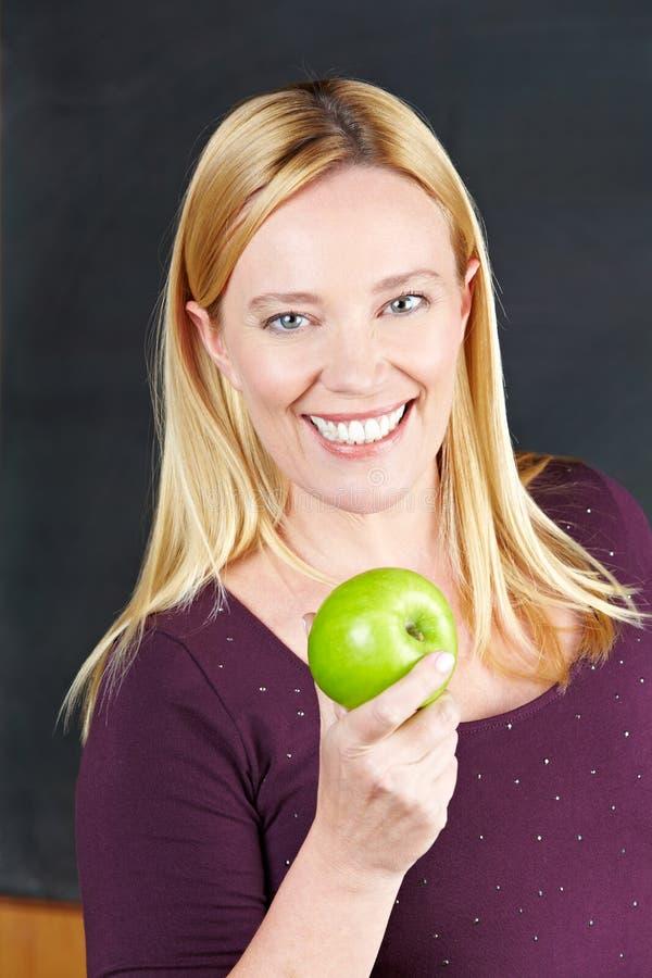 Insegnante femminile sorridente con la mela fotografie stock