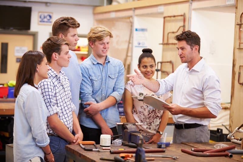 Insegnante Helping College Students che studia impianto idraulico fotografia stock libera da diritti