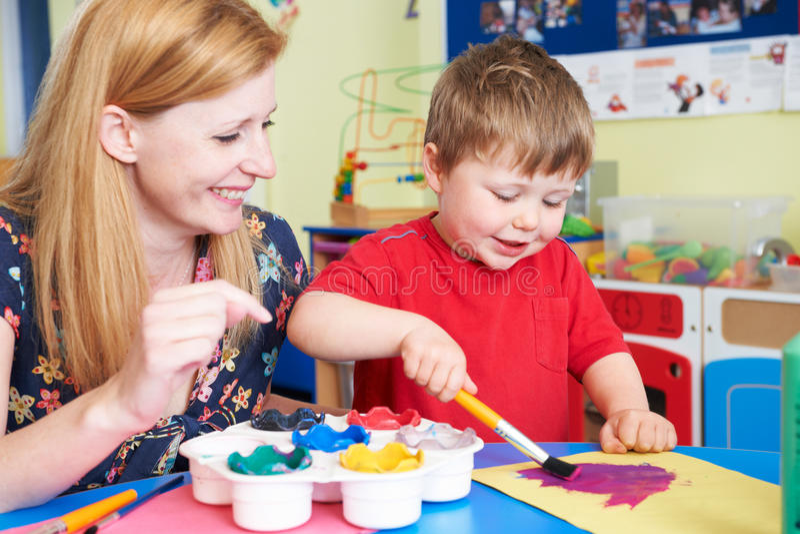 Insegnante Helping Preschool Child in Art Class immagini stock libere da diritti