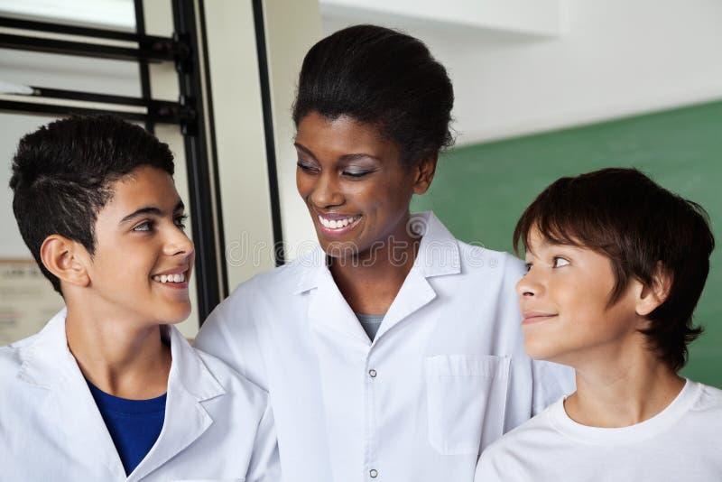 Insegnante Looking At Schoolboy nel laboratorio di scienza fotografia stock