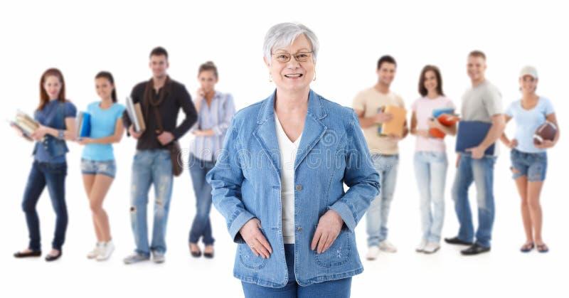 Insegnante maggiore felice con gli allievi nella priorità bassa immagine stock