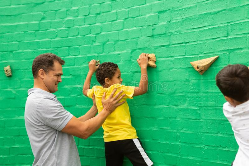 Insegnante maschio che assiste uno scolaro per scalare parete artificiale immagine stock libera da diritti