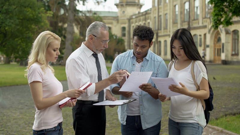 Insegnante maschio che discute i risultati dei test con gli studenti multi-etnici, lavoro di squadra immagine stock libera da diritti