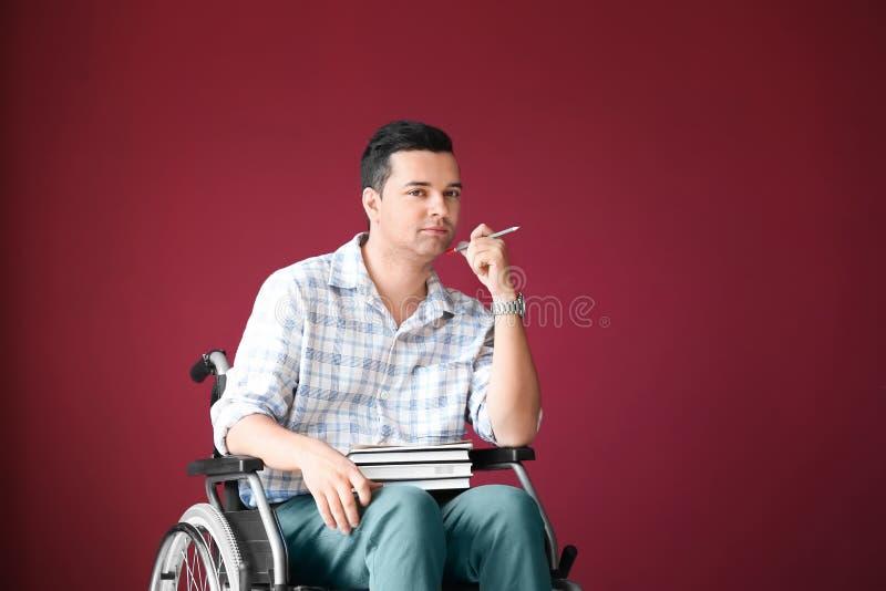 Insegnante maschio in sedia a rotelle con i libri sul fondo di colore immagine stock libera da diritti