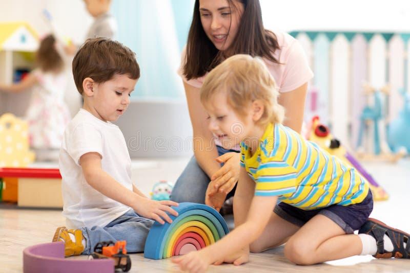 Insegnante prescolare con i bambini che giocano con i giocattoli di legno variopinti all'asilo fotografia stock