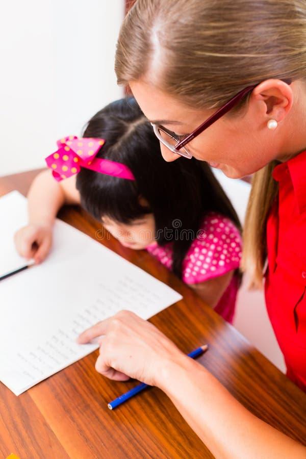 Insegnante privato inglese che lavora con la ragazza asiatica immagini stock