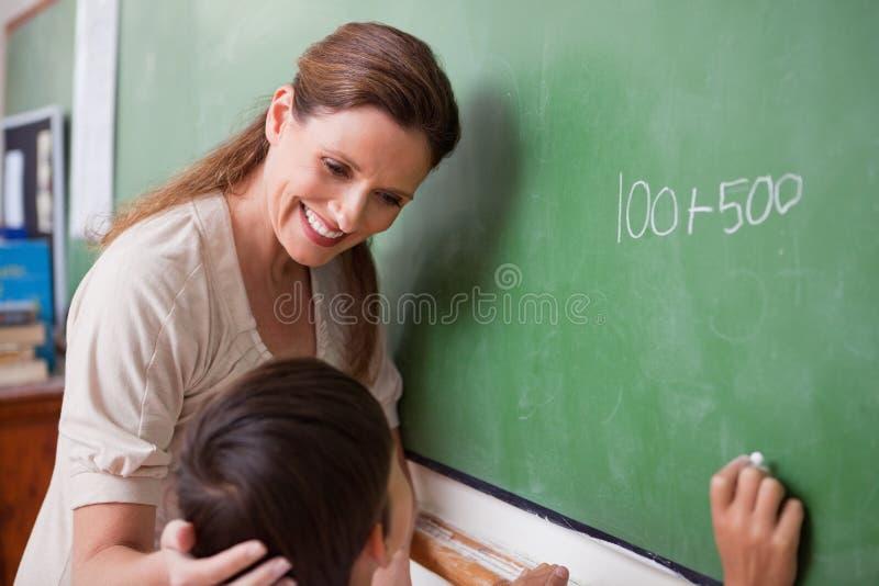 Insegnante sorridente che aiuta uno scolaro immagine stock