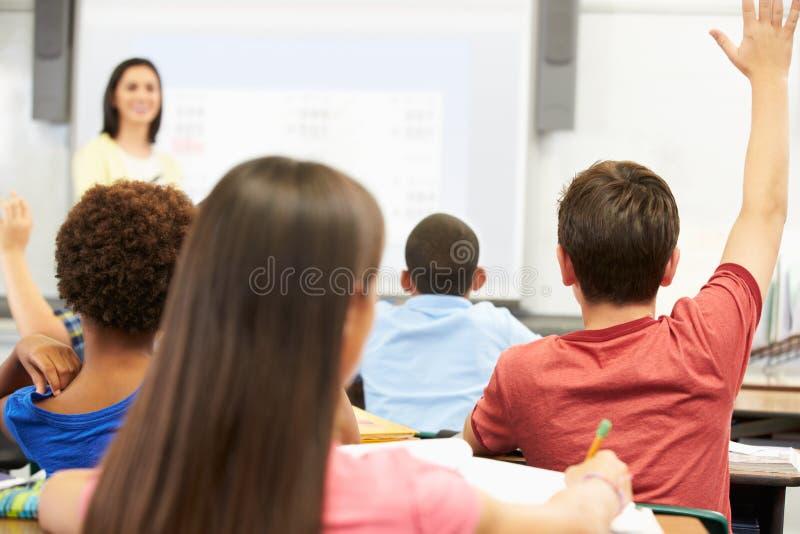 Insegnante Standing In Front Of Class Asking Question fotografia stock libera da diritti