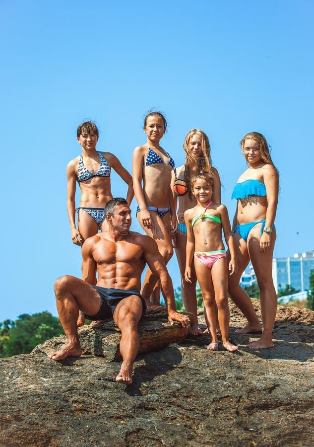 Insegnante su forma fisica con gli allievi su una spiaggia fotografia stock libera da diritti