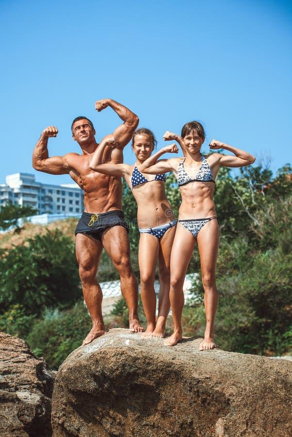 Insegnante su forma fisica con gli allievi su una spiaggia immagini stock