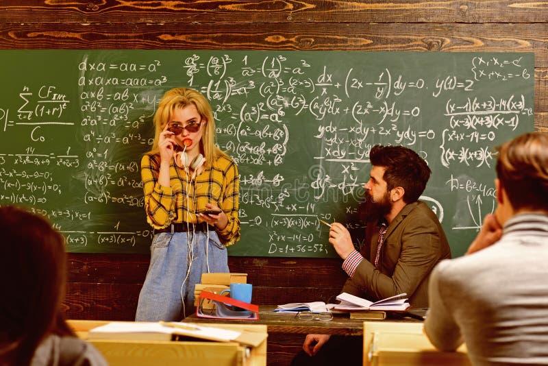 Insegnante in vetri che legge i rapporti degli studenti di talento che correggono gli errori Studenti attenti che scrivono qualco fotografia stock