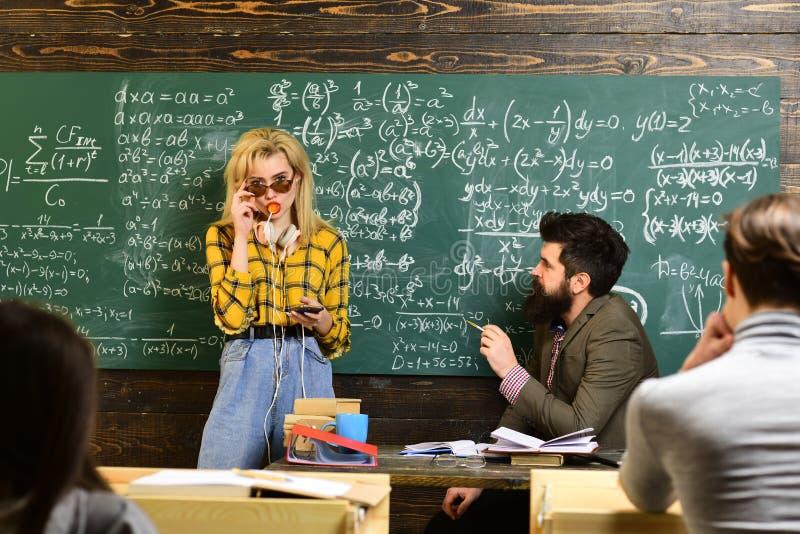 Insegnante in vetri che legge i rapporti degli studenti di talento che correggono gli errori Studenti attenti che scrivono qualco fotografia stock libera da diritti