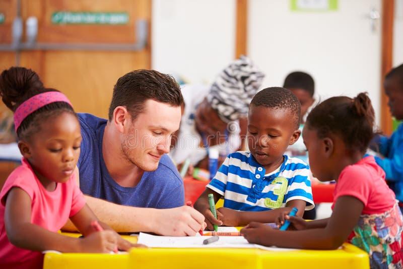 Insegnante volontario che si siede con i bambini prescolari in un'aula immagini stock