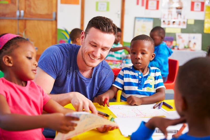 Insegnante volontario che si siede con i bambini prescolari in un'aula fotografia stock