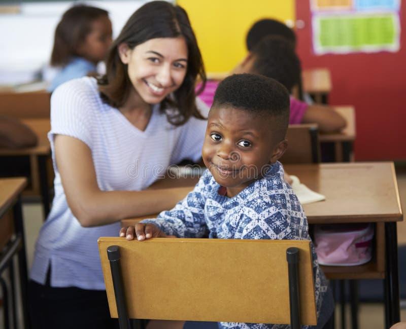 Insegnante volontario della femmina e ragazzo della scuola elementare che sorride alla macchina fotografica fotografia stock