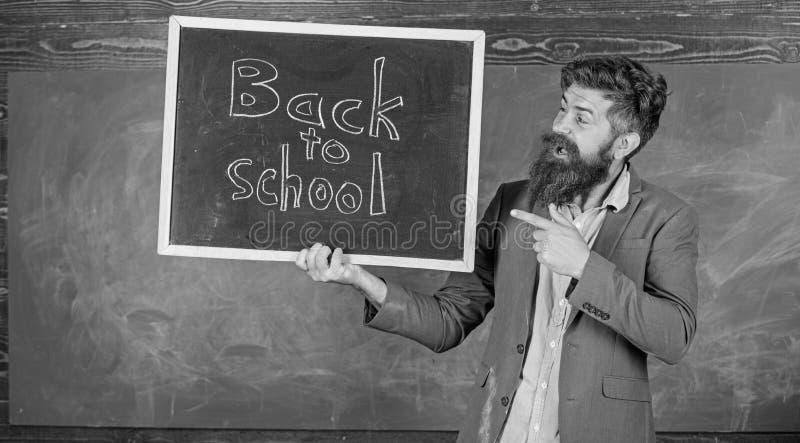 Insegnanti di noleggio per il nuovo anno scolastico Iscrizione barbuta della lavagna delle tenute dell'uomo di nuovo alla scuola  fotografie stock libere da diritti