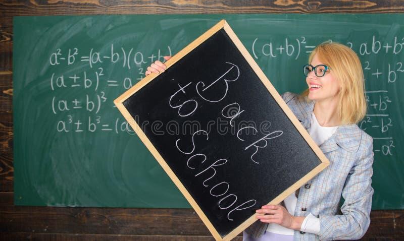 Insegnanti di noleggio per il nuovo anno scolastico L'insegnante della donna tiene l'iscrizione della lavagna di nuovo alla scuol fotografie stock