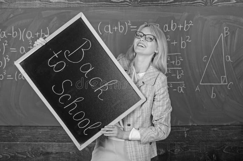 Insegnanti di noleggio per il nuovo anno scolastico L'insegnante della donna tiene l'iscrizione della lavagna di nuovo alla scuol immagini stock libere da diritti