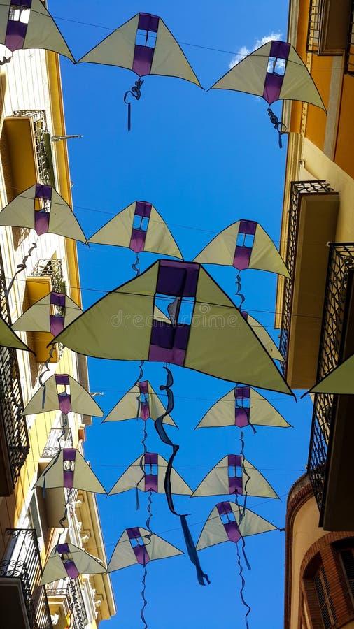 Insegne sotto forma di aquiloni gialli contro un cielo blu luminoso, Reus, Spagna immagini stock