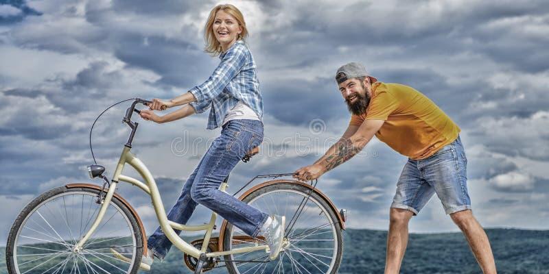 Insegni all'adulto a guidare la bici Equilibrio del ritrovamento La donna guida il fondo del cielo della bicicletta Come imparare immagini stock