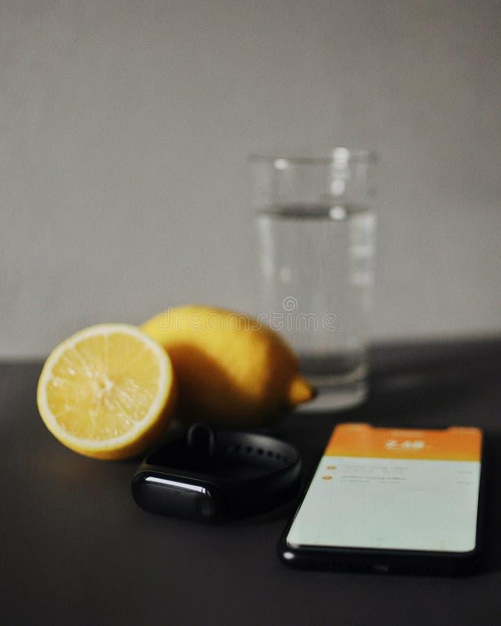 Inseguitore di Fitnes con lo smartphone che si trova sulla tavola con acqua ed il limone immagine stock