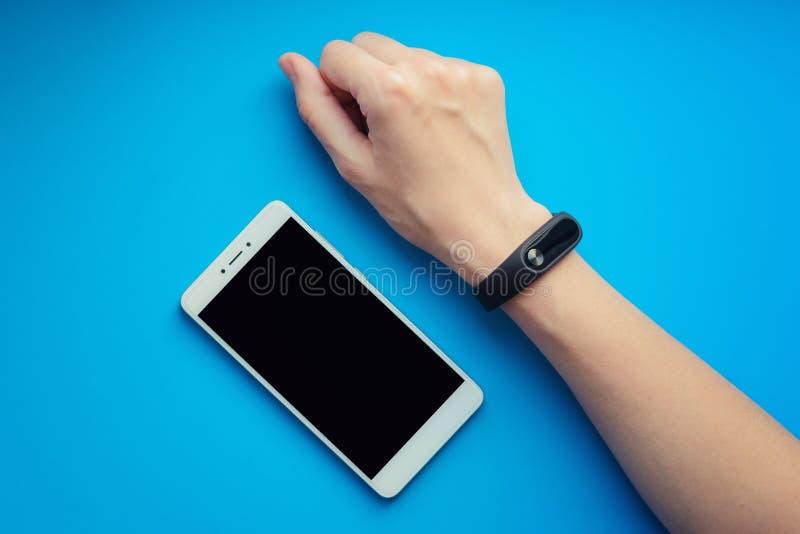 Inseguitore di forma fisica sulla mano femminile su fondo e sullo smartphone arancio immagine stock libera da diritti